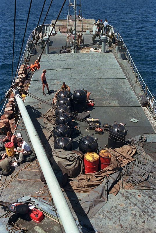 Contact mines partially covered by a tarpaulin on the deck of the captured Iranian mine-laying ship TRAN AJR.