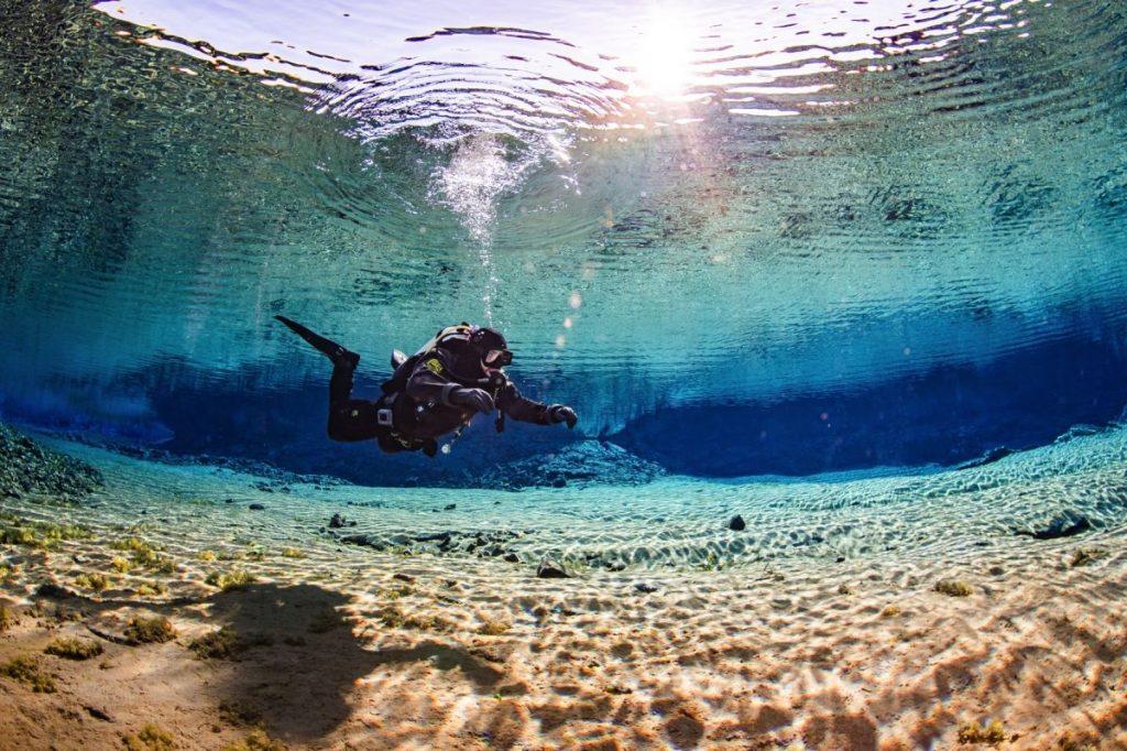 Questa immagine ha l'attributo alt vuoto; il nome del file è diver-fraser-cameron-flying-in-silfra-lagoon-sunreflections-by-anders-nyberg-1199x799-q80-1024x682.jpg